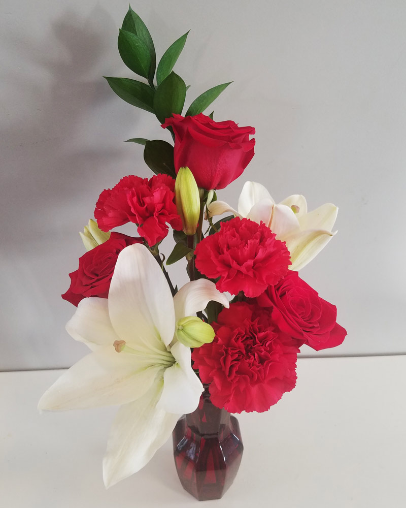 cheap Christmas flower arrangement with white lilies, red roses, and red carnations in a clear vase