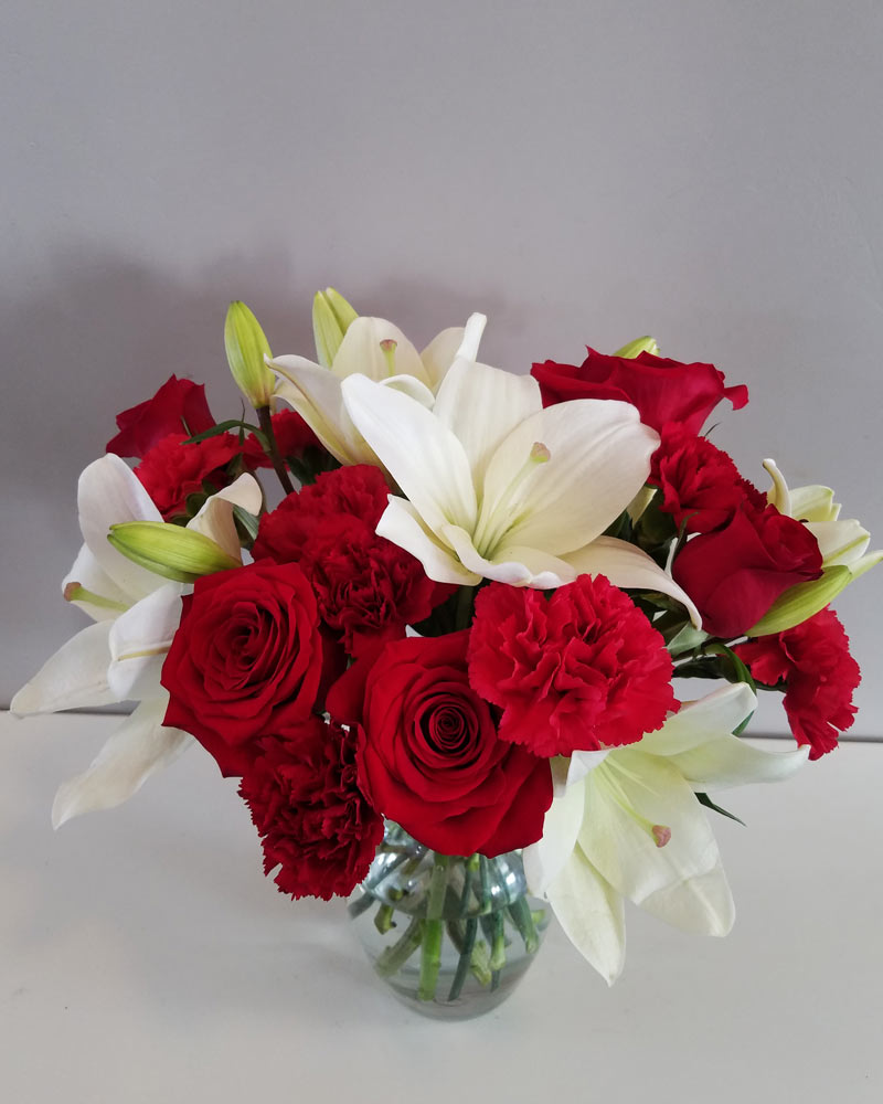 extra large Christmas flower arrangement with white lilies, red roses, and red carnations in a clear vase