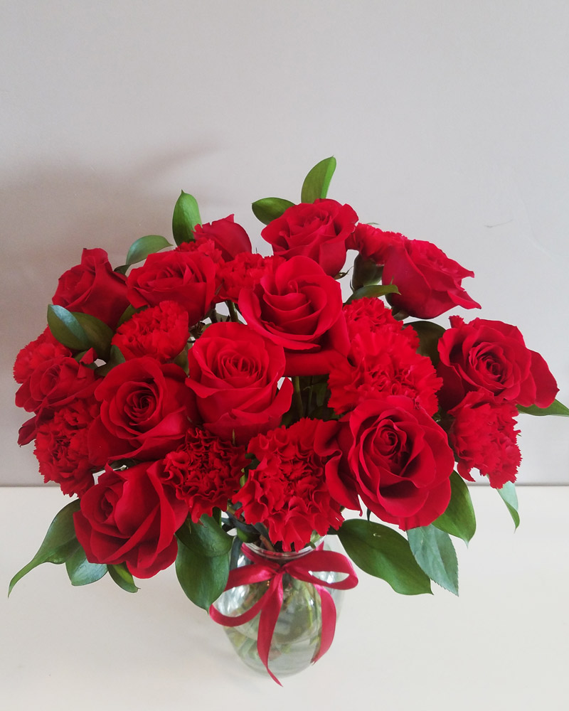 One Dozen Red Roses and one dozen red carnations flower arrangement in a clear vase