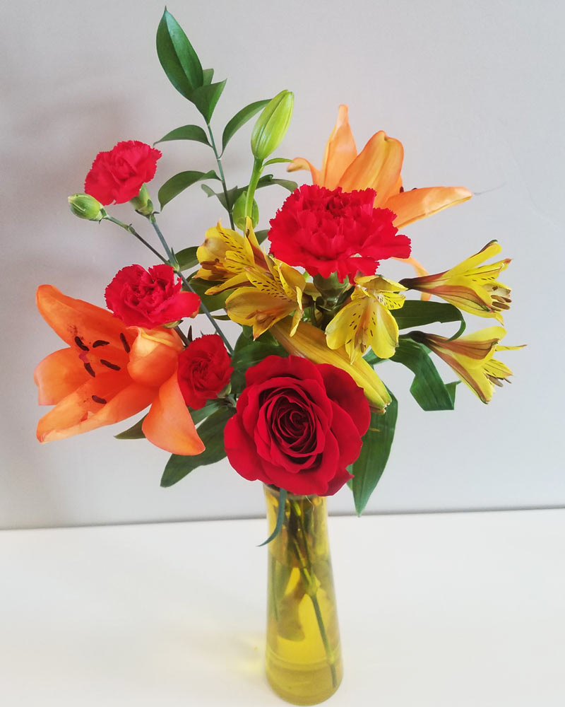 cheap flower arrangement with orange lilies and red roses and red carnations in a yellow vase